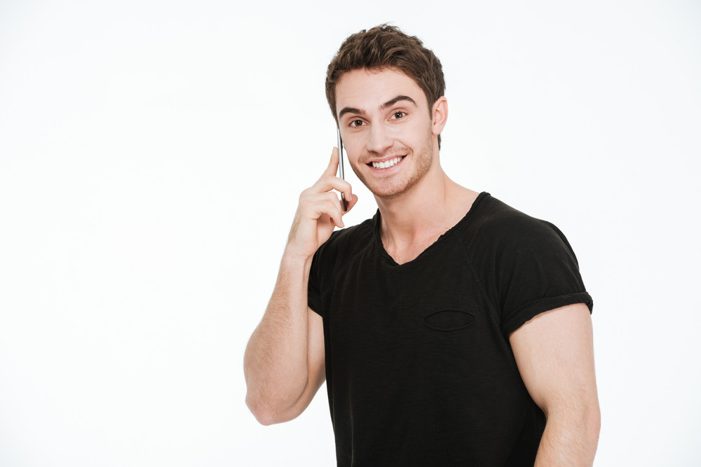 Image of smiling young man dressed in black t-shirt standing over white background talking by phone.