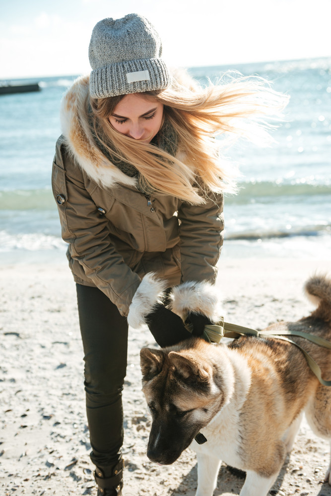 Image of smiling young woman walks in winter beach with dog on a leash.
