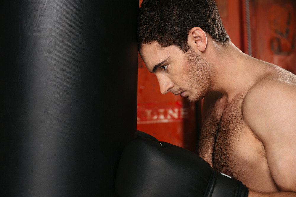Image of tired boxer standing with punchbag. Looking aside.