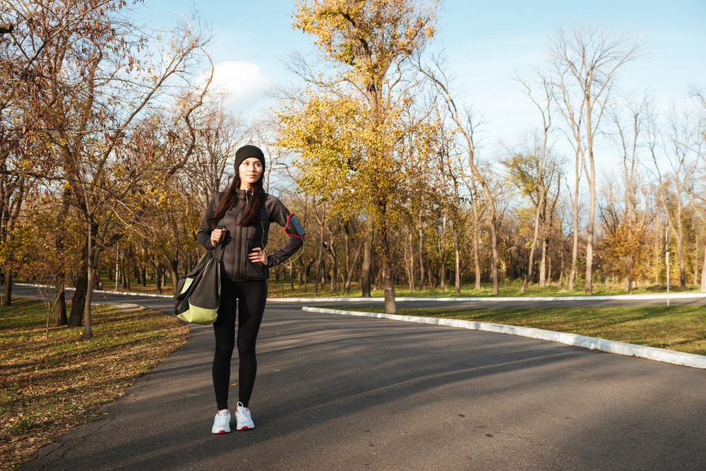 Image of woman runner in warm clothes and earphones in autumn park holding bag. Look aside.