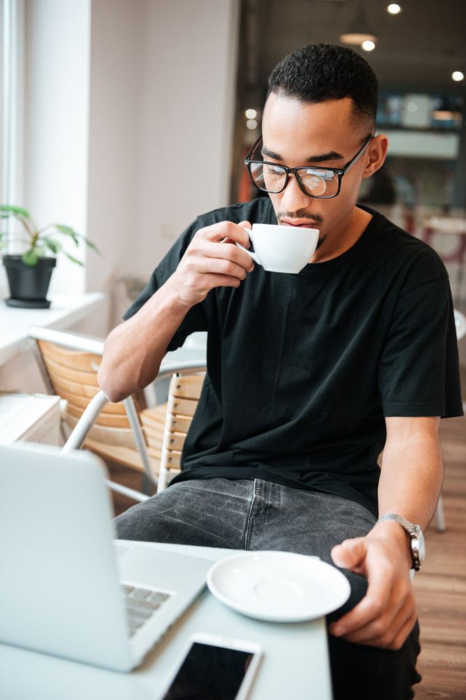 Image of young african businessman wearing glasses sitting near window and typing by laptop computer while drinking coffee. Coworking.