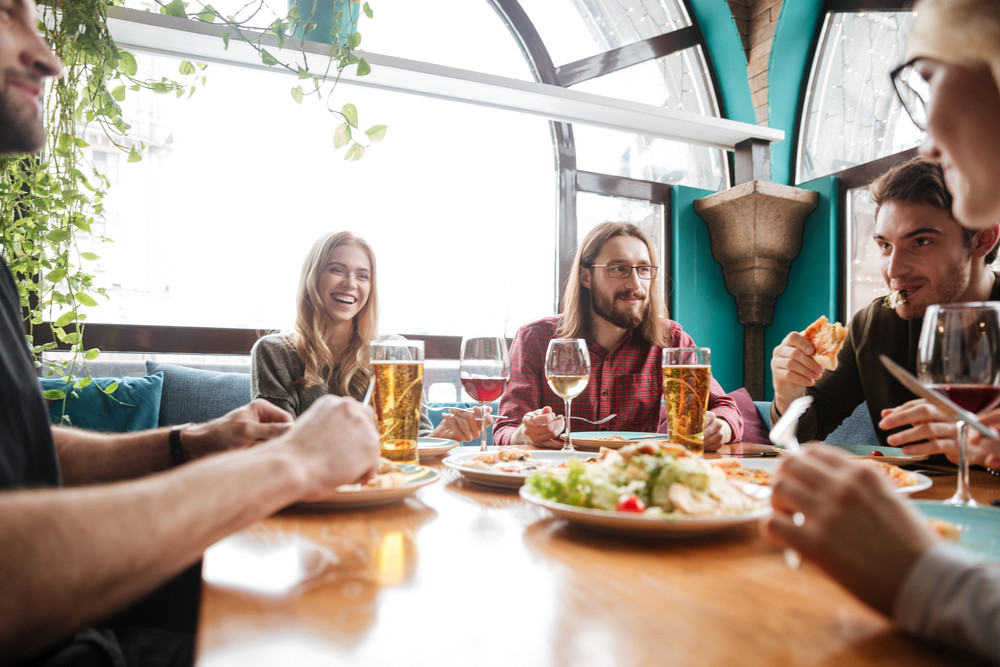 Image of young attractive friends sitting in cafe eating pizza while drinking alcohol.
