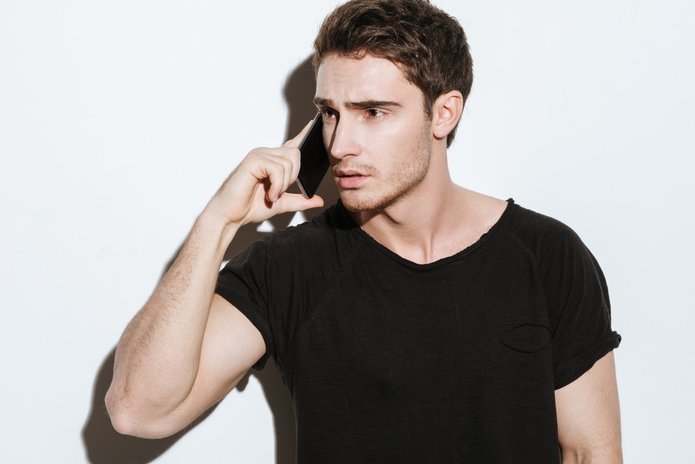 Image of young attractive man dressed in black t-shirt posing over white background and talking by phone. Looking aside.