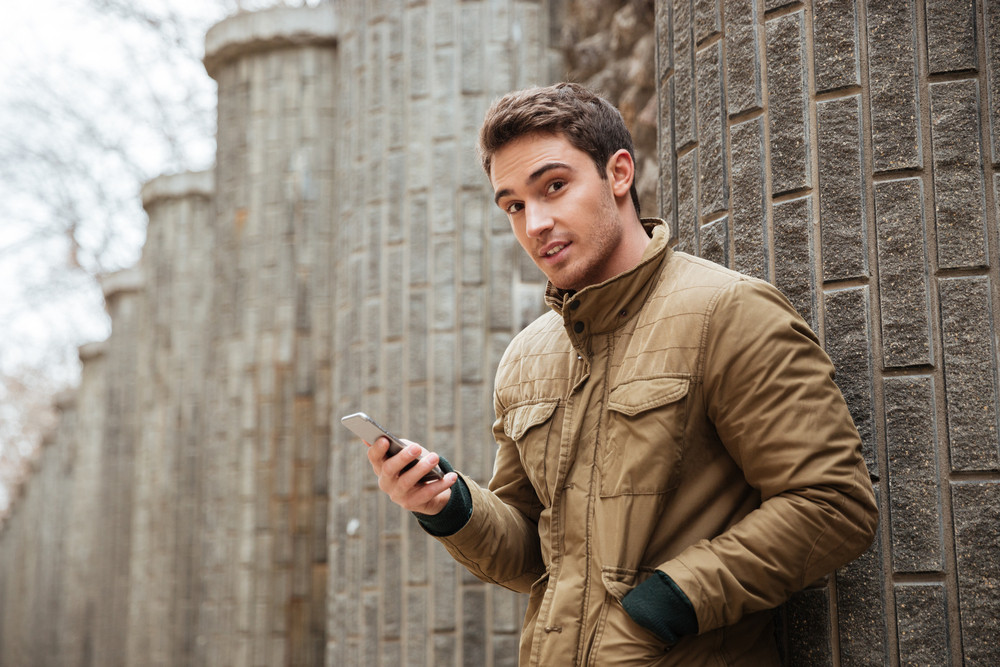 Image of young attractive man walking on the street and chatting by his phone outdoors. Look at camera.