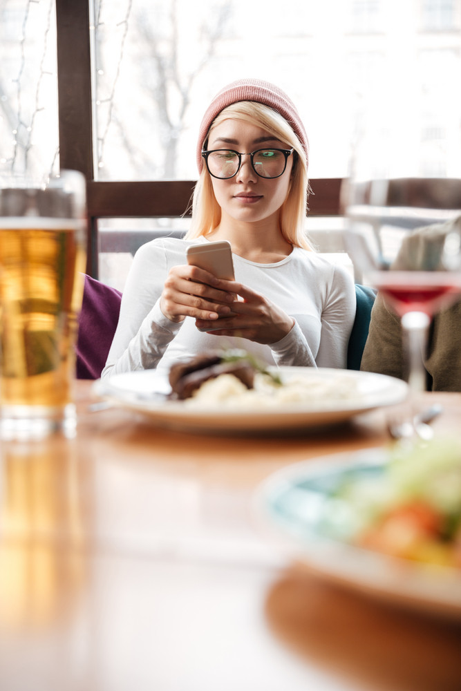 Image of young attractive woman sitting in cafe while using mobile phone. Looking at phone.
