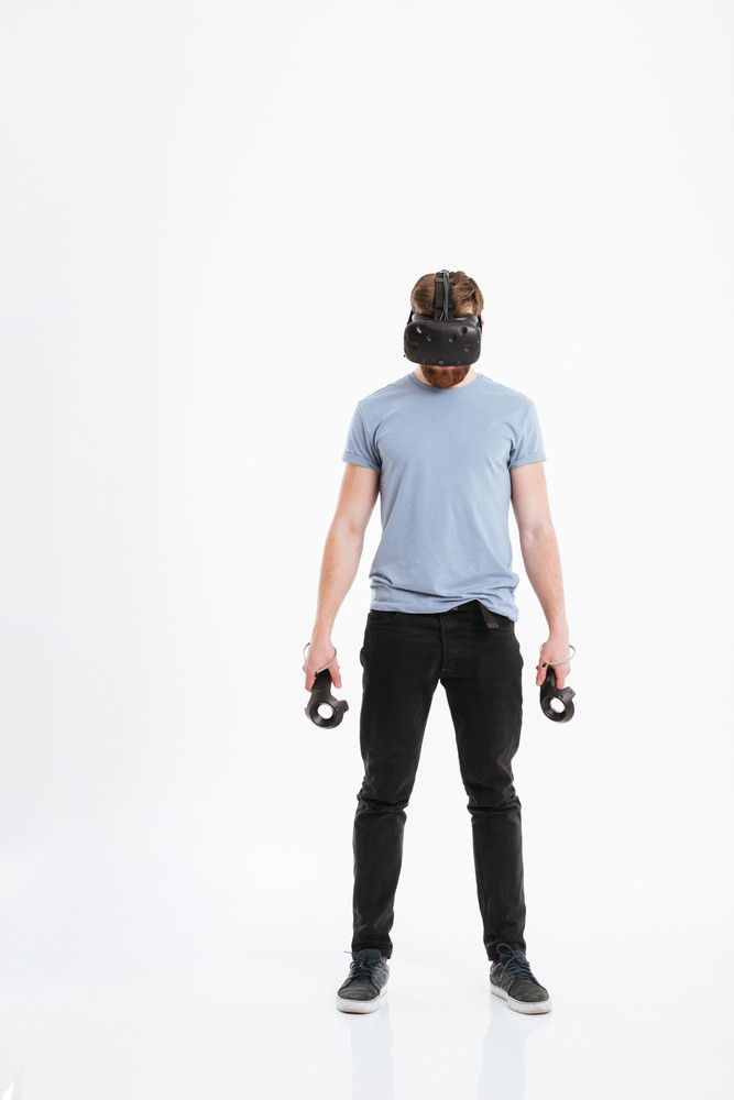 Image of young bearded man wearing virtual reality device standing over white background with joysticks