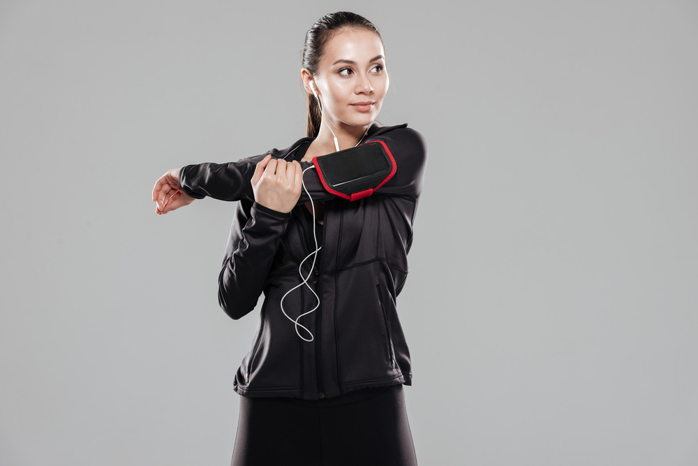 Image of young beautiful fitness lady standing over grey background listening music with earphones.