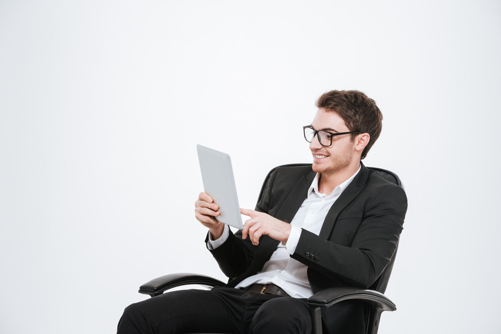 Image of young businessman sitting on chair at studio using tablet computer. Isolated over white background. Look at tablet.