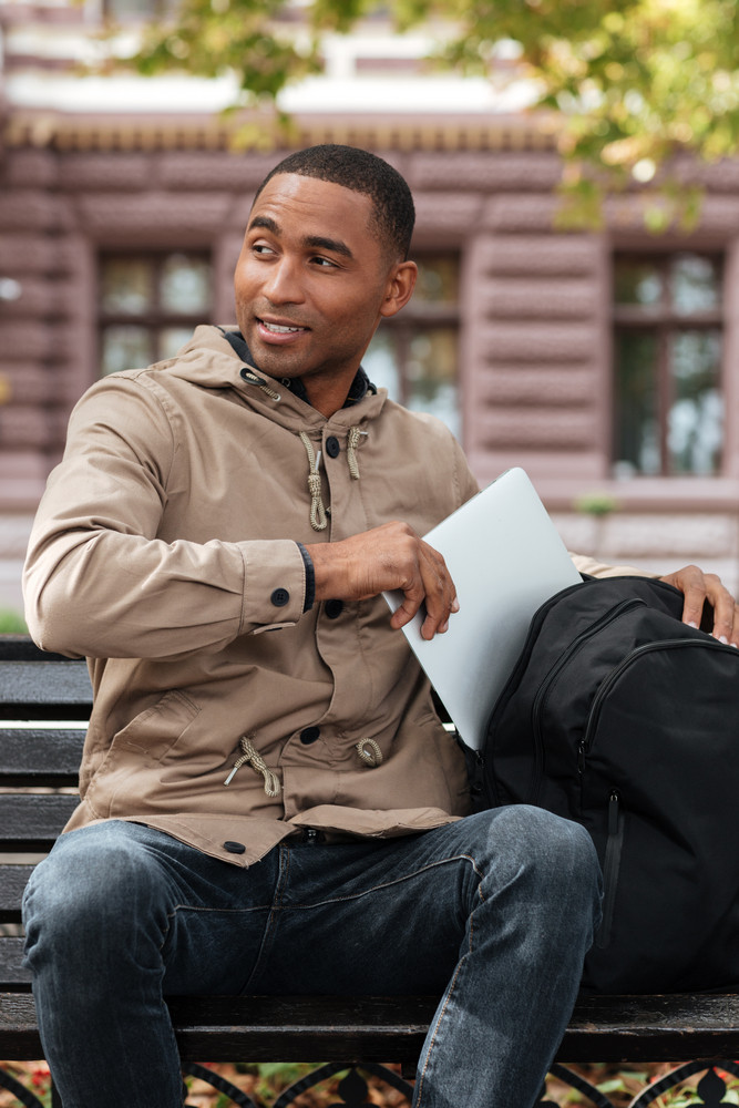 Image of young cheerful african man getting laptop from backpack. Look aside.