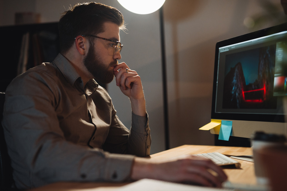 Image of young concentrated bearded web designer dressed in shirt working late at night and looking at computer.
