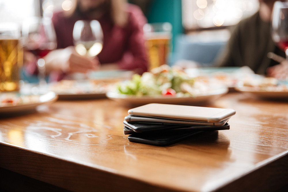 Image of young friends sitting in cafe eating pizza while drinking alcohol. Focus on lot of mobile phones on table.