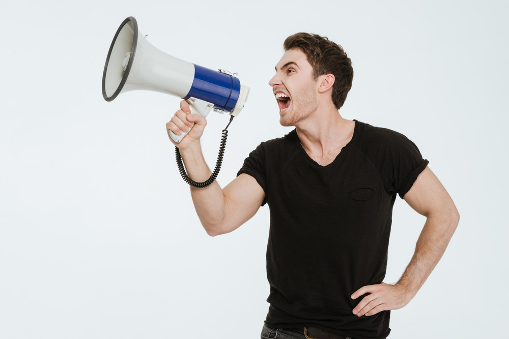 Image of young handsome man dressed in black t-shirt standing over white background screaming with mouthpiece.