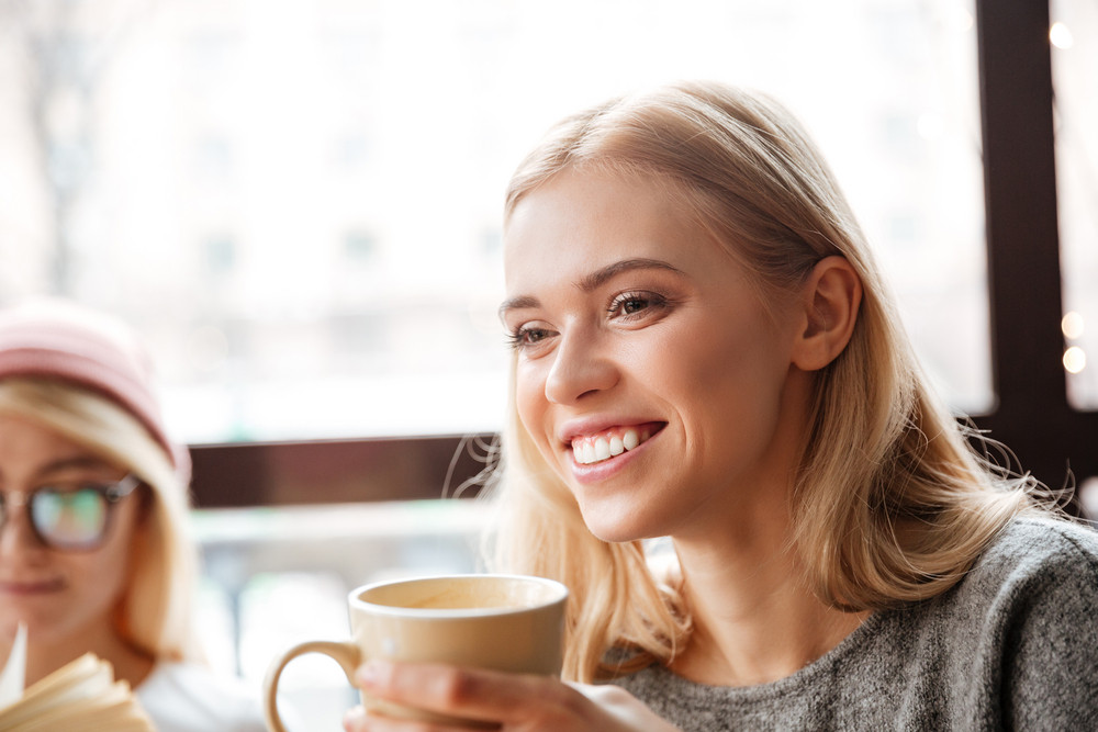 Image of young happy woman sitting in cafe and drinking coffee. Looking aside.