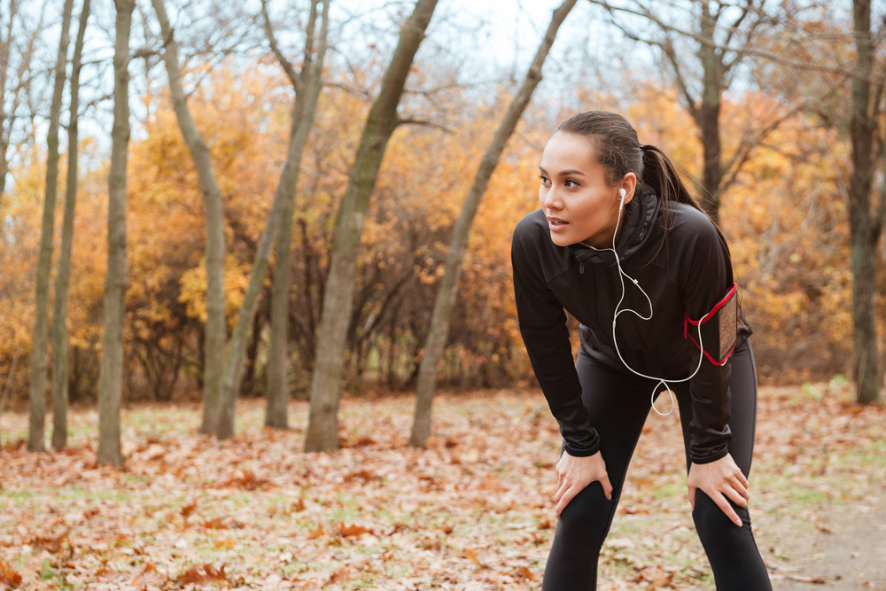 Image of young lady runner in warm clothes and earphones running in autumn park
