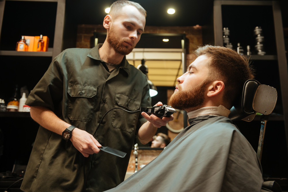 Image of young man getting beard haircut by hairdresser while sitting in chair at barbershop.