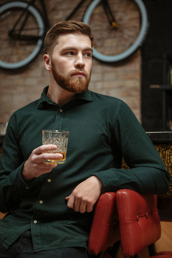 Image of young man sitting in an armchair and drinking whiskey . Look aside.