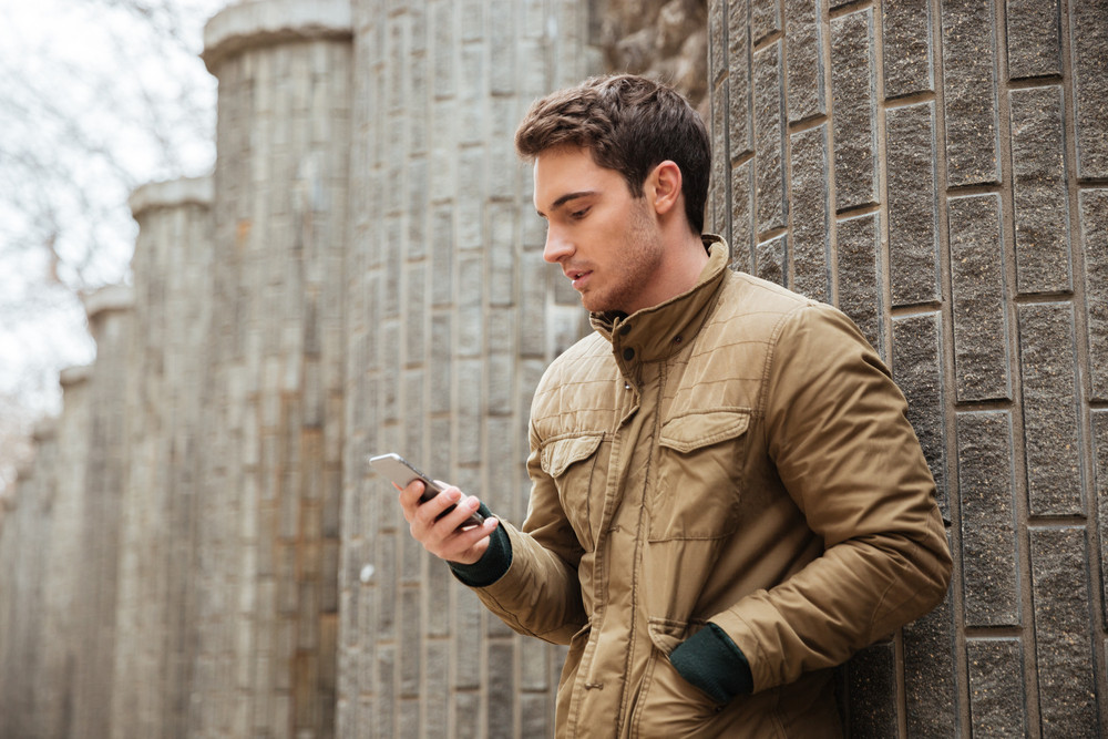 Image of young man walking on the street and chatting by his phone outdoors. Look at phone.