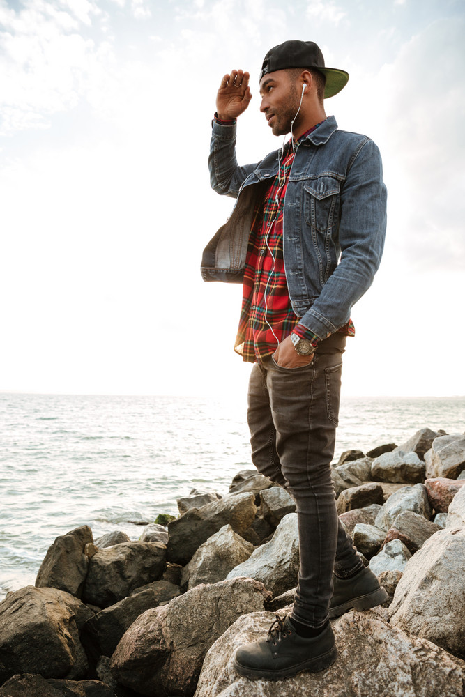 Image of young man wearing cap walking on the beach while listening music with earphones. Look at sea.
