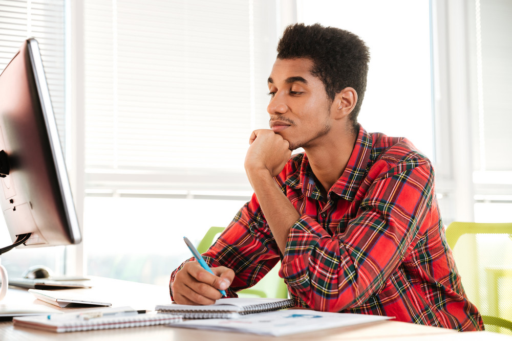 Image of young smart african student writing notes in notebook while sitting and looking at computer