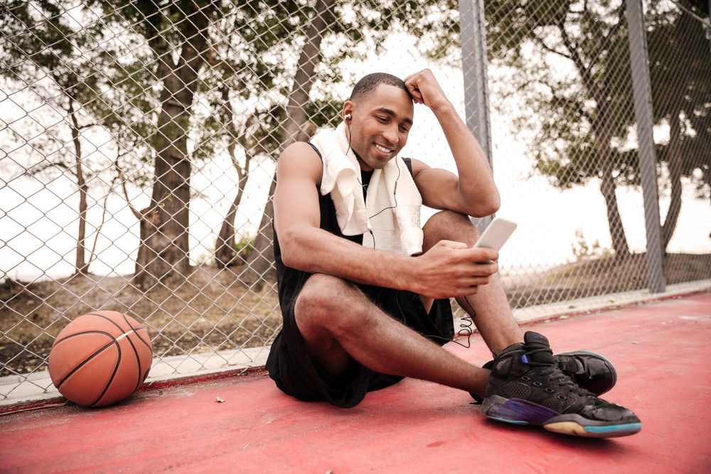 Image of young smiling african basketball player sitting in the park with towel near basketball and chatting while listen to music. Look at phone.