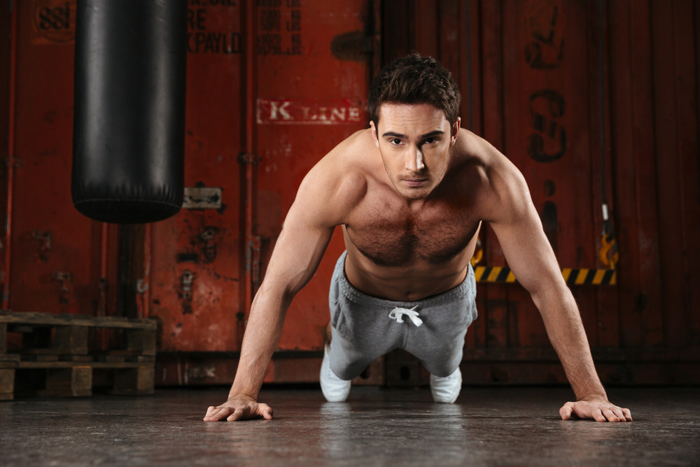 Image of young strong man make sport exercises in a gym. Looking at camera.