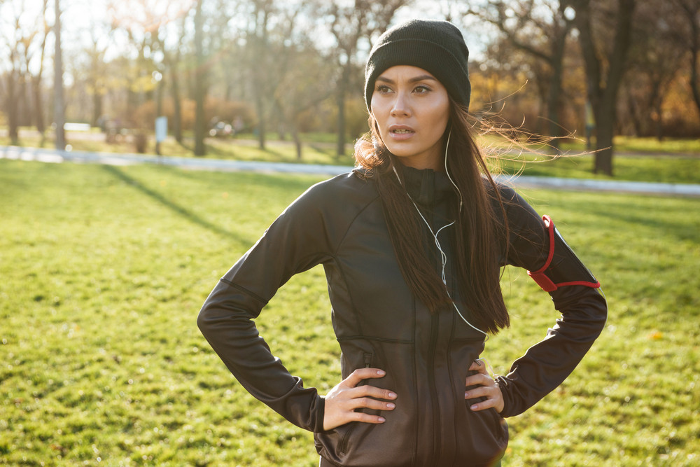 Image of young woman runner in warm clothes and earphones in autumn park. Look aside.