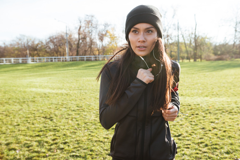 Image of young woman runner in warm clothes and earphones running in autumn park