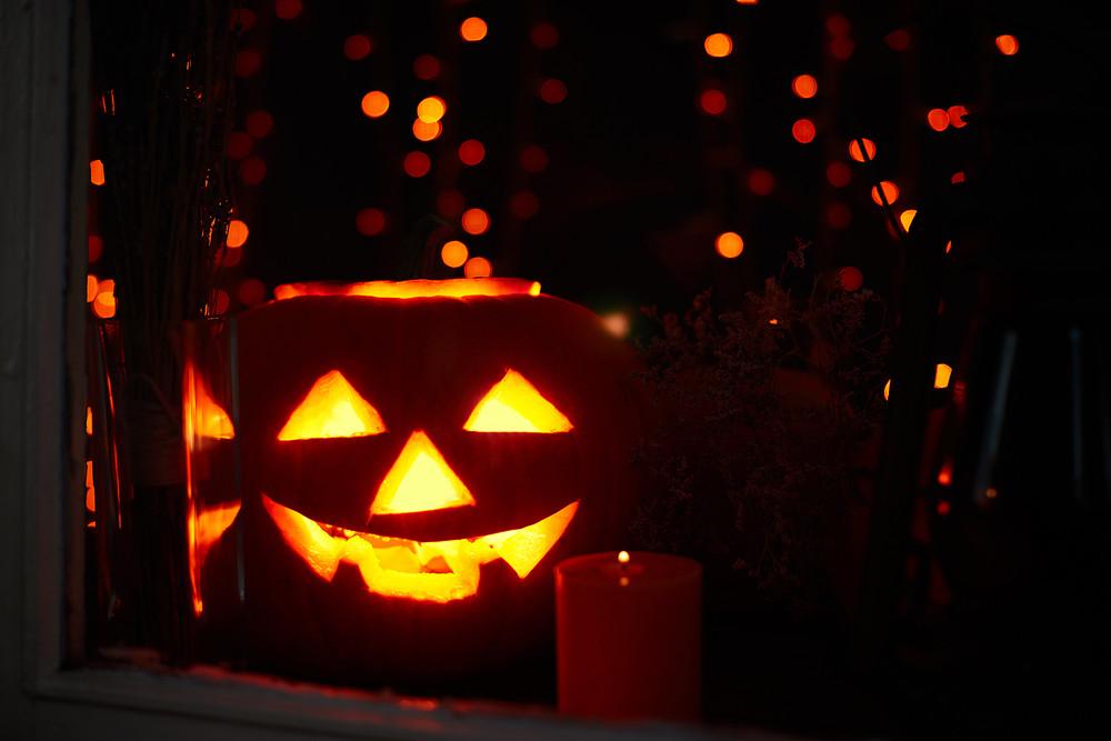 Jack-o-lantern and burning candle near by