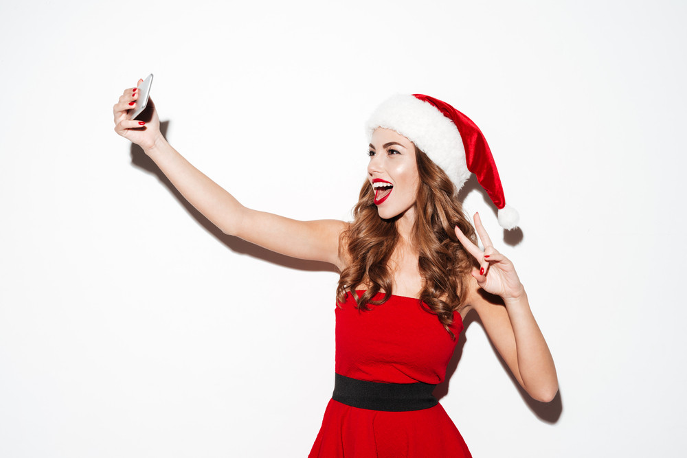 Joyful pretty young woman in red santa claus costume making selfie using her cellphone over white background