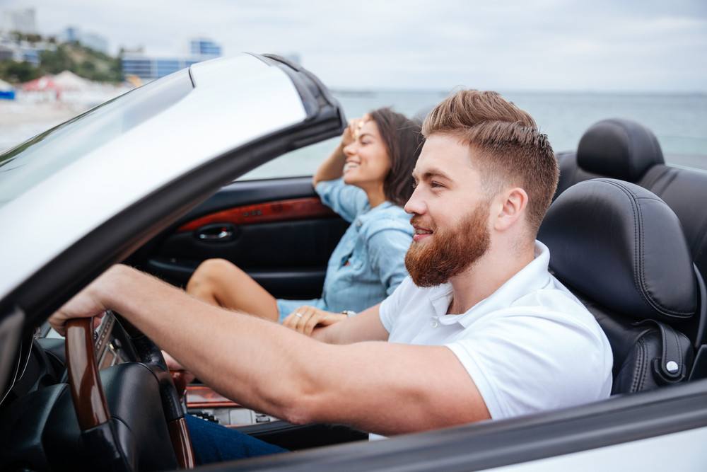 Joyful young couple smiling while riding in their convertible car