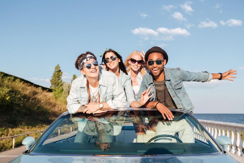 Joyful young friends having fun in cabriolet