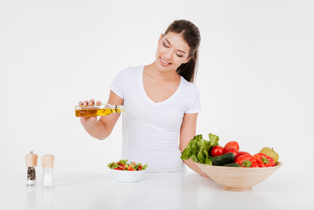 Joyful young woman cooking with vegetables and oil. Isolated on white background.