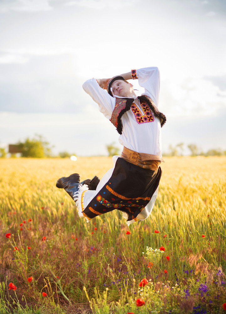 Jumping man in the sunset field. He is wearing traditional Eastern Europe folk costumes.