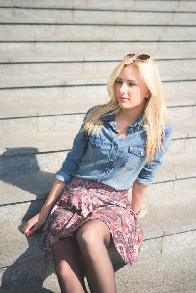 4387e6491dd Knee figure of a young beautiful blonde girl posing seated on a staircase  outdoor in the ...