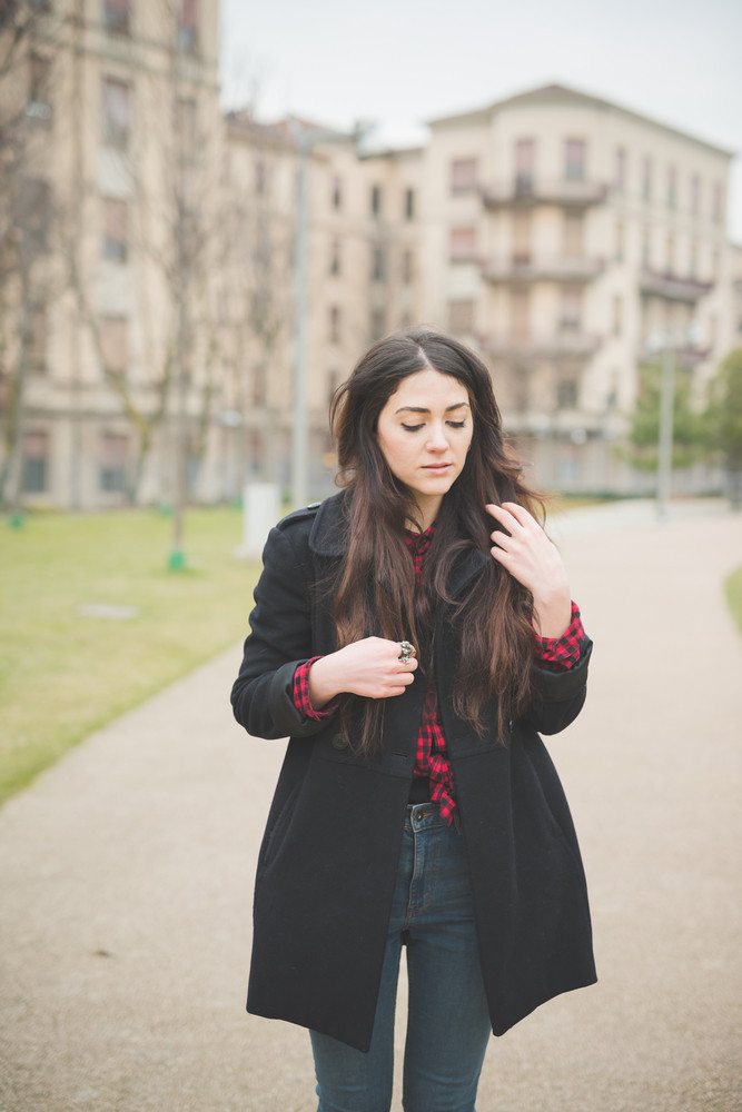 Knee figure of a young beautiful brunette long hair woman pensive and melancholic looking downward touching her hair - concept of humans emotions