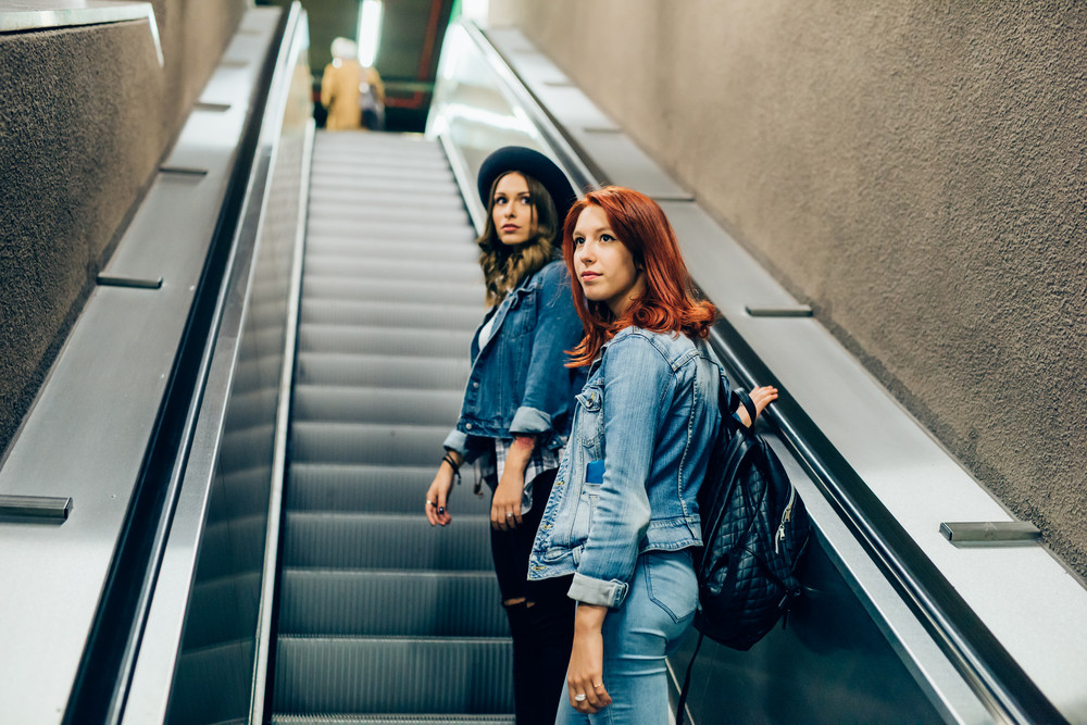 Knee figure of two young handsome caucasian blonde and redhead straight hair women using escalator in the subway, both overlooking pensive - thoughtful, serious, transport concept