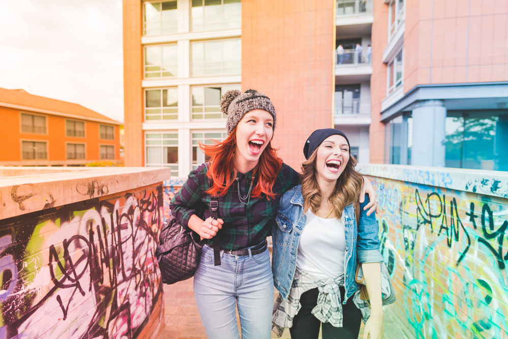 Knee figure of two young handsome caucasian blonde and redhead straight hair women walking hugging outdoor in the city, laughing, looking in camera - having fun, carefree, youth concept - colorful filtered