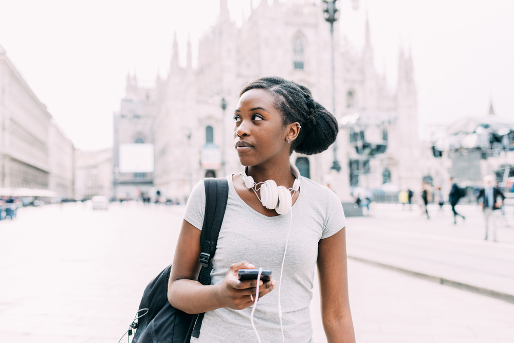 Knee figure of young beautiful black woman walking outdoor in the city, headphones around her neck and smart phone hand hold, looking over serene - technology, carefree, music concept