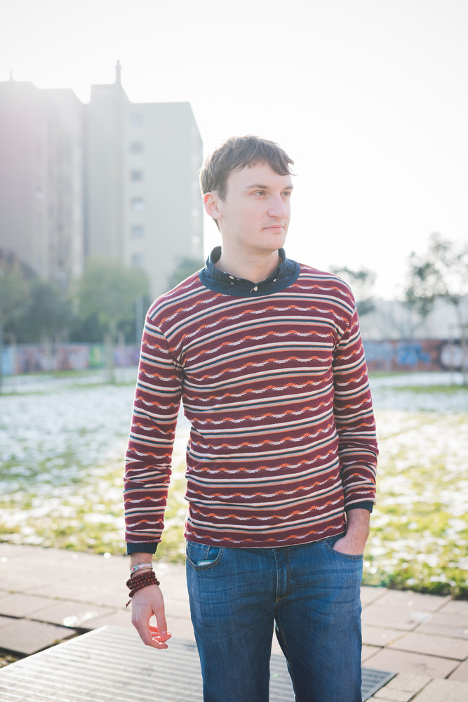 Knee figure of young handsome man overlooking left in the city, wearing blue jeans and a red striped sweater, hands in pocket - pensive, thoughtful concept