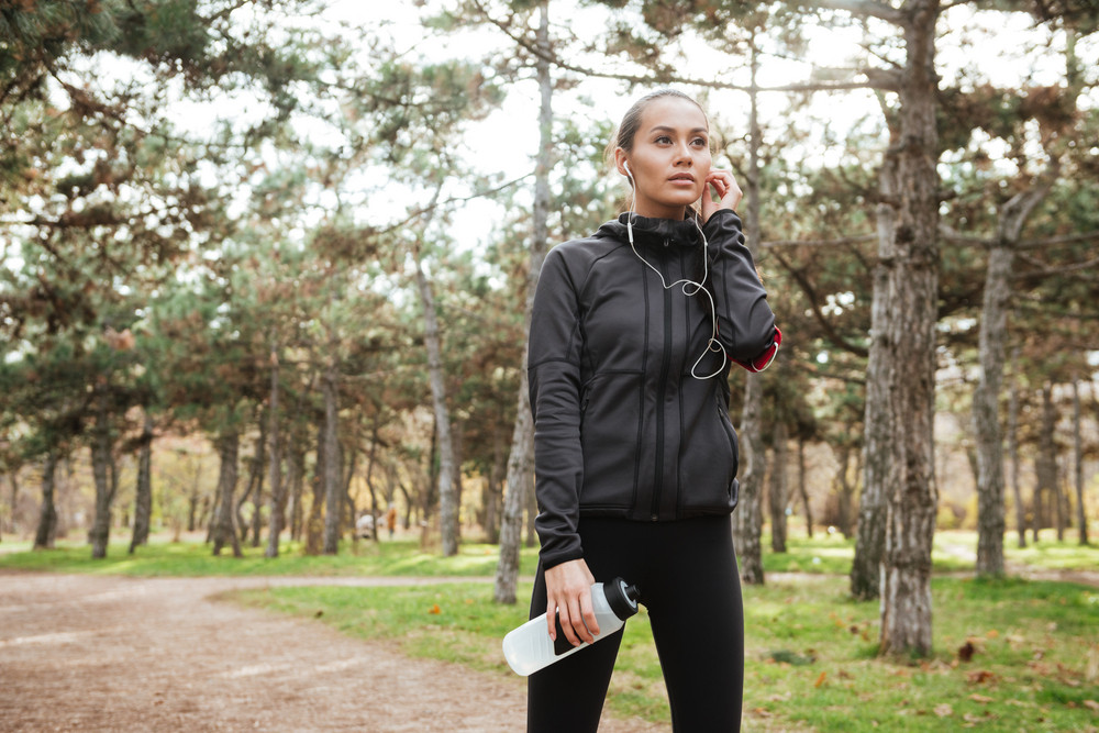 Lady runner in warm clothes looking aside in autumn park while holding bottle of water and touching earphones