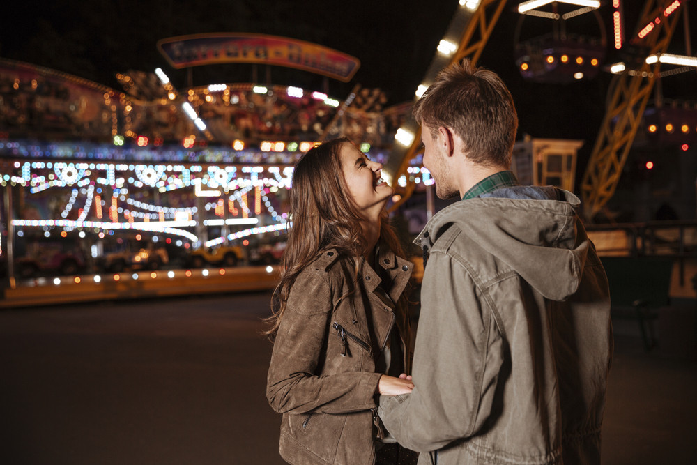 Laughing couple in amusement park. in warm clothes