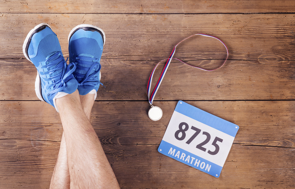 Legs of a runner, medal and race number on a wooden floor background