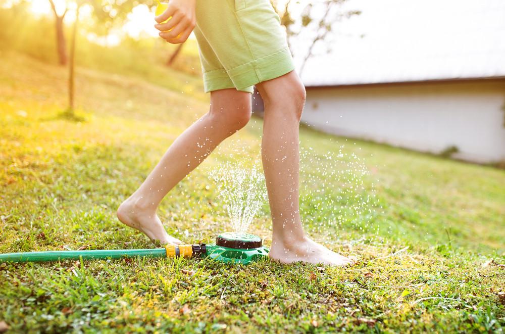 Legs of a young boy in a summer garden
