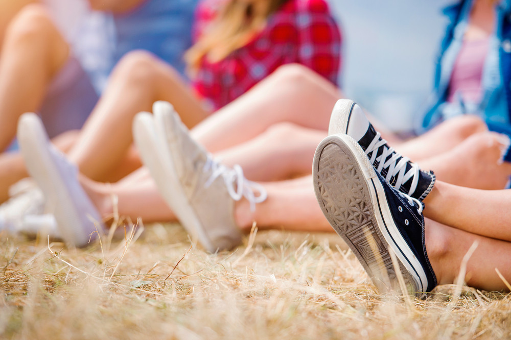 Legs of teenagers at summer music festival, canvas shoes, sitting on the grass in front of stage