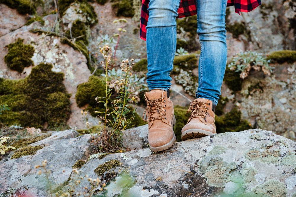 Legs of traveling girl on rock. cropped image