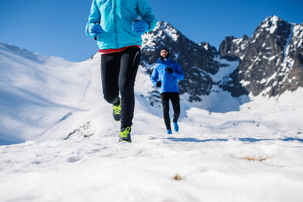 Legs of two runners outside in winter nature