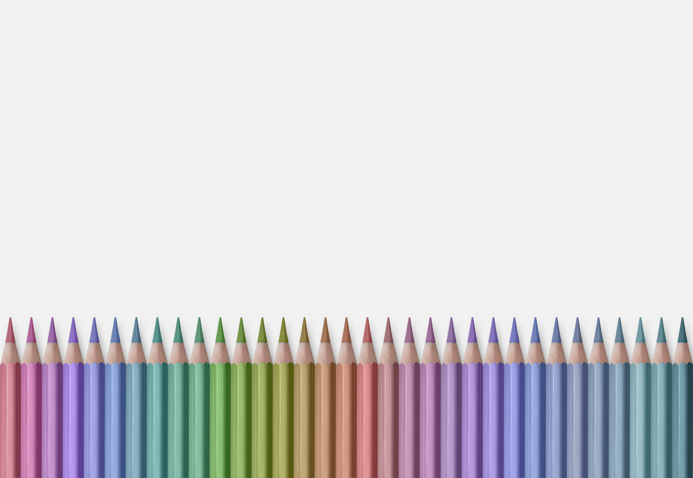 line of colored pencils isolated on white background