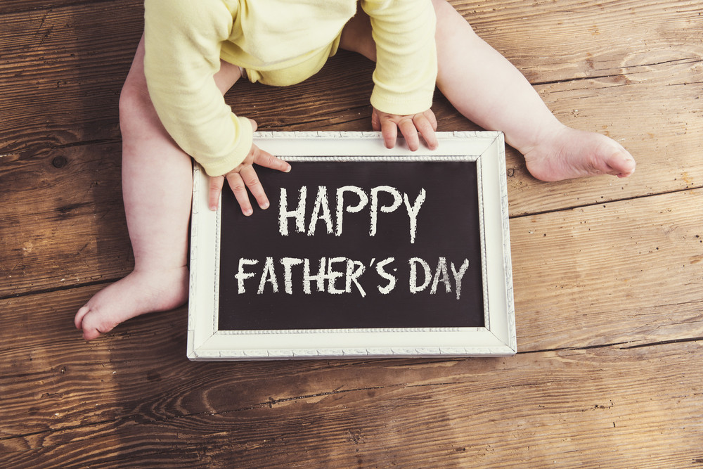 Little baby with Happy fathers day sign on wooden background