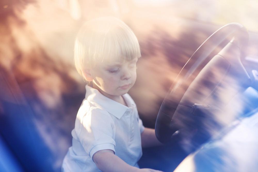 Little boy driving a car. He is having fun.