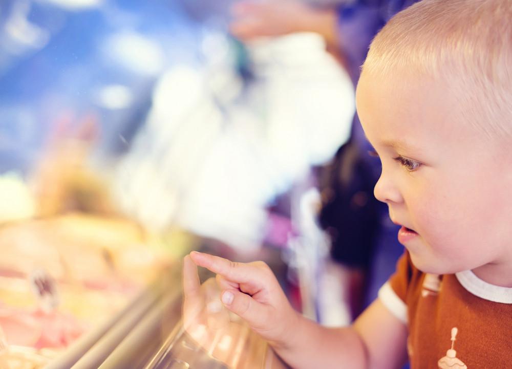 Little boy enjoying ice cream in cafe